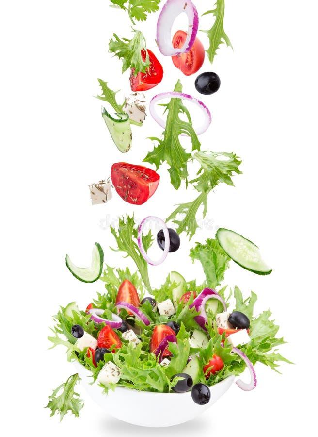 Insalata fresca con gli ingredienti delle verdure di volo immagini stock