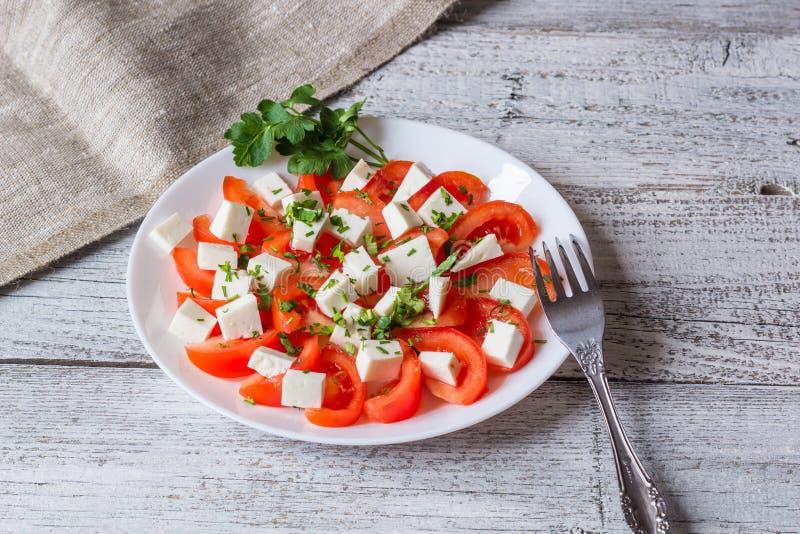Insalata fresca con il pomodoro, la mozzarella e le erbe fotografia stock