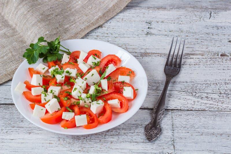 Insalata fresca con il pomodoro, la mozzarella e le erbe immagine stock