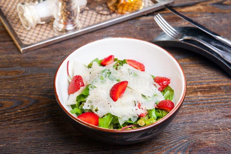 Insalata fresca con la fragola, gli spinaci ed il formaggio in una ciotola su fondo di legno Tavola servita del ristorante con la fotografie stock libere da diritti