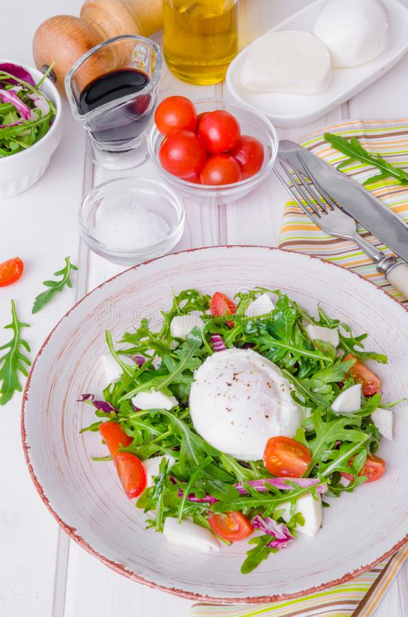 Insalata fresca con la rucola, la mozzarella, i pomodori ciliegia e l'uovo affogato fotografia stock