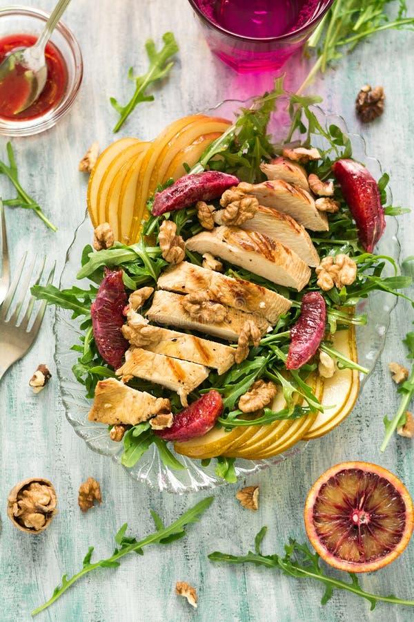 Insalata fresca della molla con il petto di pollo arrostito, rucola, pera e fette e noci arancio fotografia stock