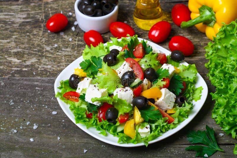 Insalata greca con gli ortaggi freschi, il feta e le olive nere su un fondo di legno fotografia stock libera da diritti