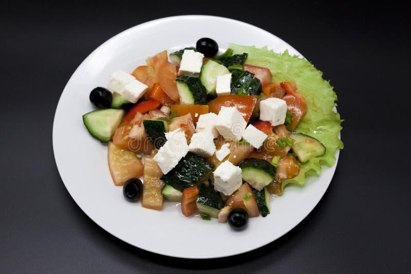 Insalata greca su un piatto bianco su un fondo nero Può essere usato come foto per i menu del ristorante, bistrot Europeo, il Med immagine stock