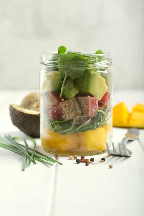 Insalata hawaiana del colpo con il tonno, l'avocado, il mango e le verdure in un barattolo con la forcella e le verdure su un rus immagine stock
