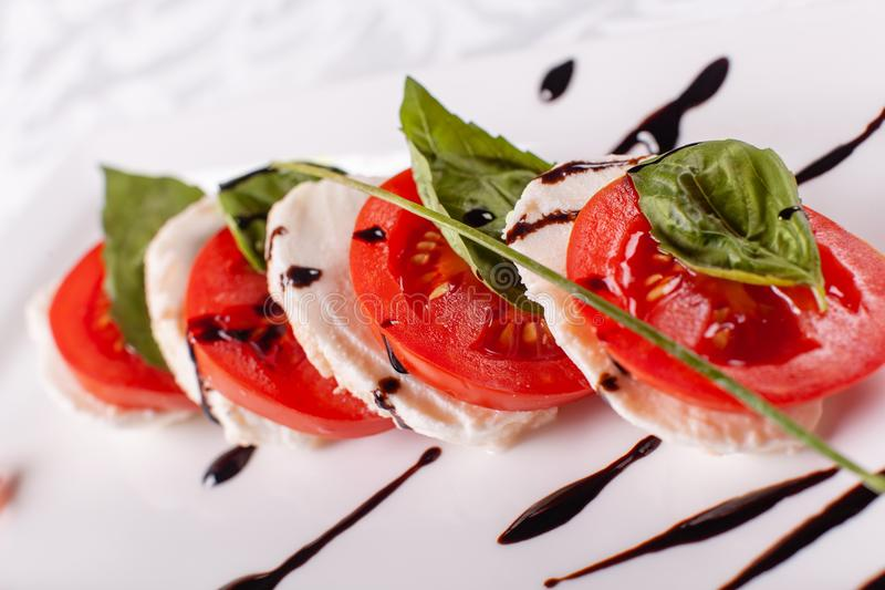 Insalata italiana di Caprese Mozzarella, pomodori e foglie dell'erba del basilico Aceto balsamico sistemato sul piatto bianco fotografia stock