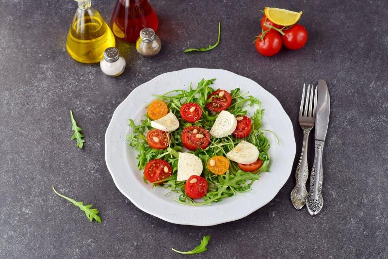 Insalata italiana tradizionale con il pomodoro ciliegia, ruccola, mozzarella, aceto di vino dell'olio d'oliva su un piatto bianco fotografia stock libera da diritti
