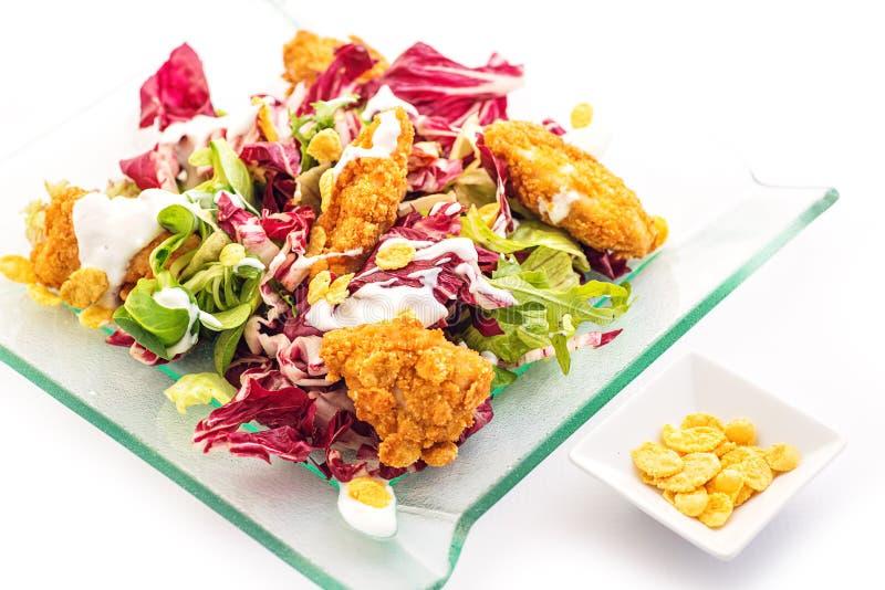 Insalata mista della lattuga con pollo fritto in fiocchi di mais sulla lastra di vetro isolata su fondo bianco, fotografia del pr immagine stock libera da diritti