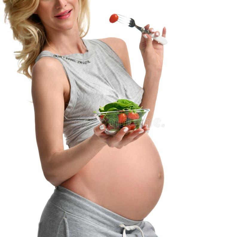 Insalata organica e forcella della bella tenuta della donna incinta con il pomodoro Cibo sano di aspettativa di maternità di grav immagini stock libere da diritti