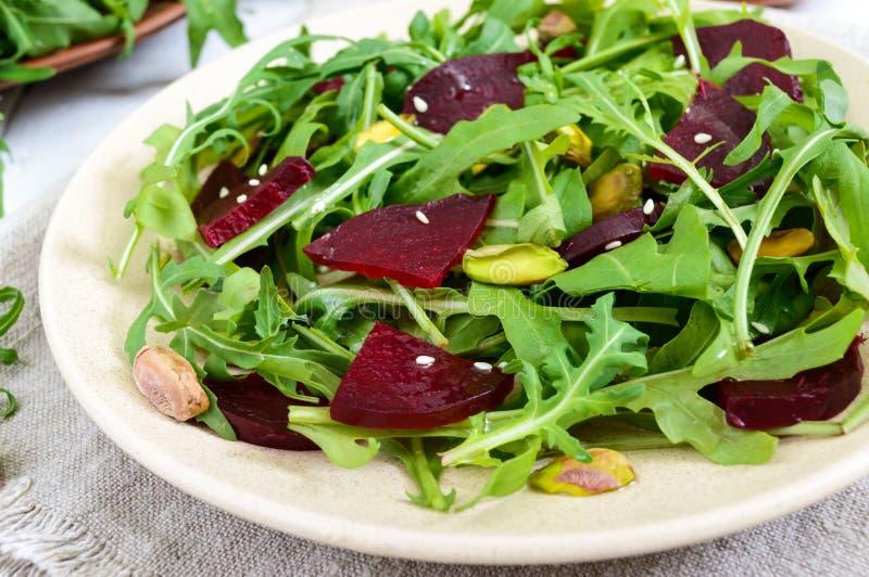 Insalata piccante del vegano delle barbabietole, rucola, pistacchi su un piatto su un fondo bianco immagini stock libere da diritti