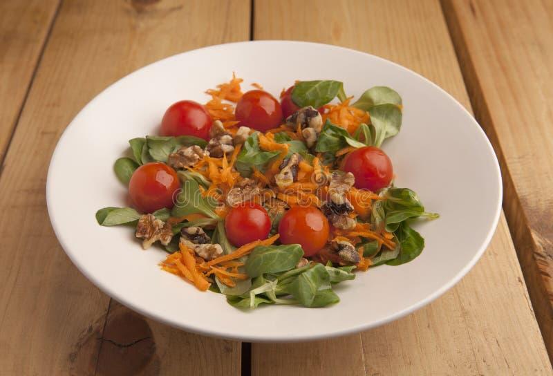 Insalata sana con i pomodori ciliegia, i canoni e la carota grattata immagine stock