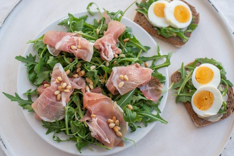 Insalata sana con il prosciutto di Parma, il pane e le foglie verdi fotografia stock