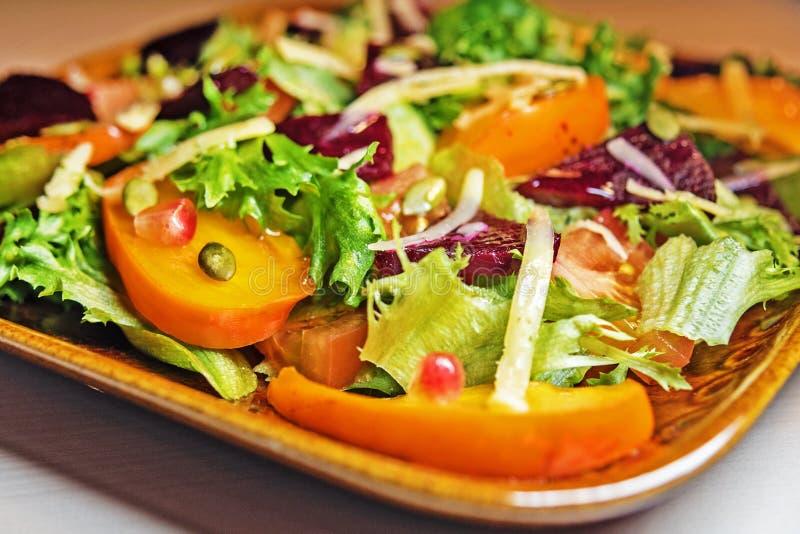 Insalata sana con l'insalata, il cachi e le barbabietole della lattuga Insalata del cachi Dieta Alimento vegetariano fotografie stock libere da diritti