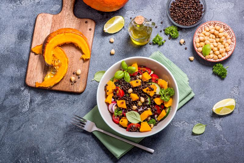 Insalata sana con la zucca arrostita, i ceci e le lenticchie nere, alimento di autunno, cibo del vegano immagine stock