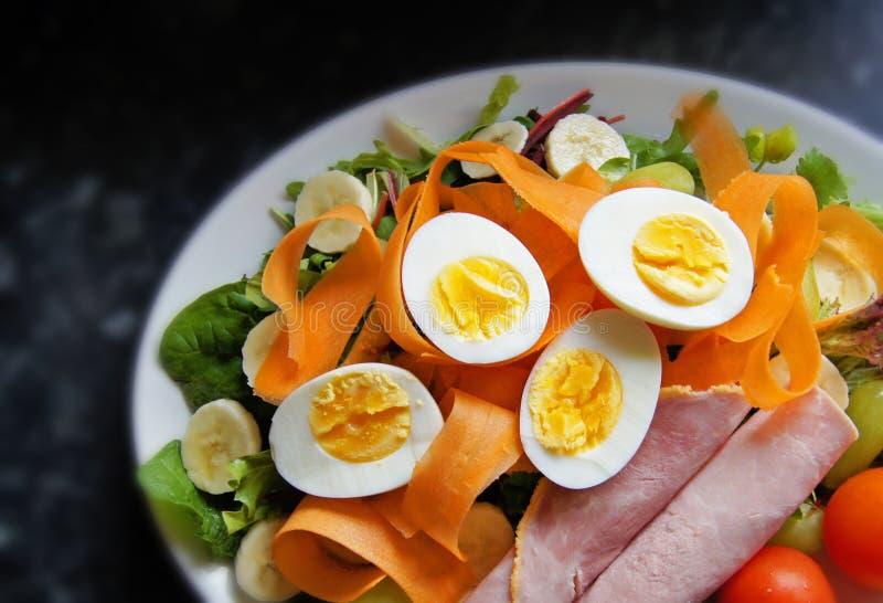 Insalata sana degli uova sode, del prosciutto, dei pomodori, delle carote, ecc sul piano di lavoro nero del granito fotografie stock libere da diritti