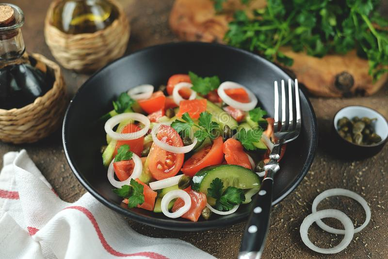 Insalata sana dei pomodori ciliegia, del cetriolo, del sedano, delle cipolle, dei capperi e del prezzemolo con il salmone salato immagine stock libera da diritti