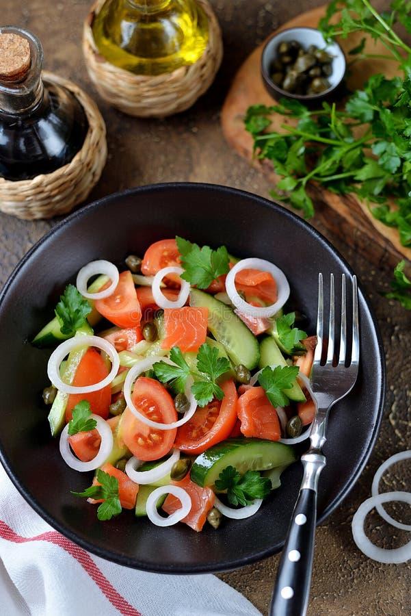 Insalata sana dei pomodori ciliegia, del cetriolo, del sedano, delle cipolle, dei capperi e del prezzemolo con il salmone salato fotografia stock libera da diritti