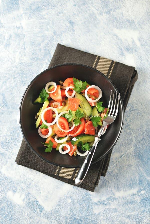 Insalata sana dei pomodori ciliegia, del cetriolo, del sedano, delle cipolle, dei capperi e del prezzemolo con il salmone salato fotografie stock libere da diritti