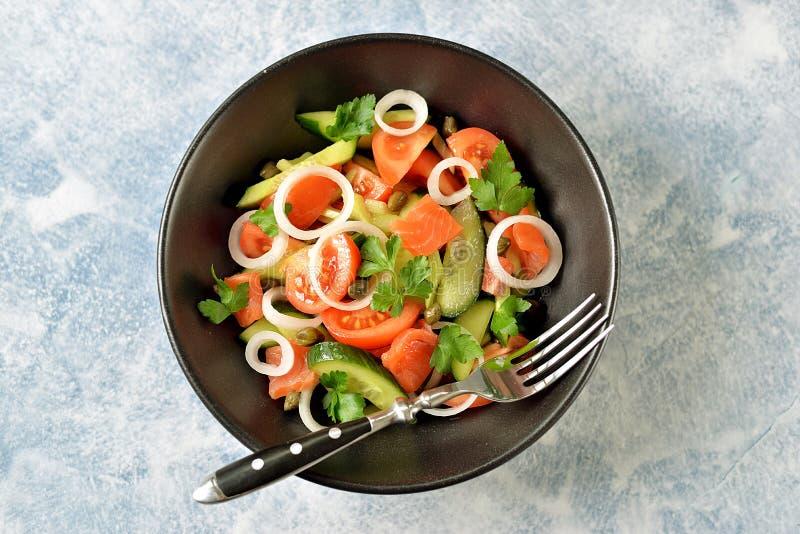 Insalata sana dei pomodori ciliegia, del cetriolo, del sedano, delle cipolle, dei capperi e del prezzemolo con il salmone salato immagini stock libere da diritti