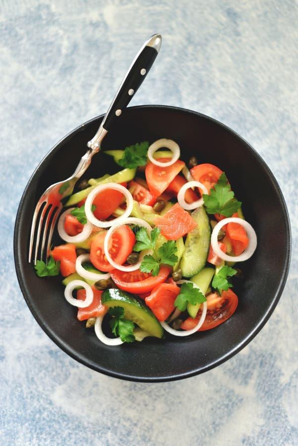Insalata sana dei pomodori ciliegia, del cetriolo, del sedano, delle cipolle, dei capperi e del prezzemolo con il salmone salato immagini stock