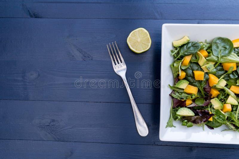 Insalata sana dell'avocado del mango con la calce della forcella e lo spazio della copia fotografia stock libera da diritti