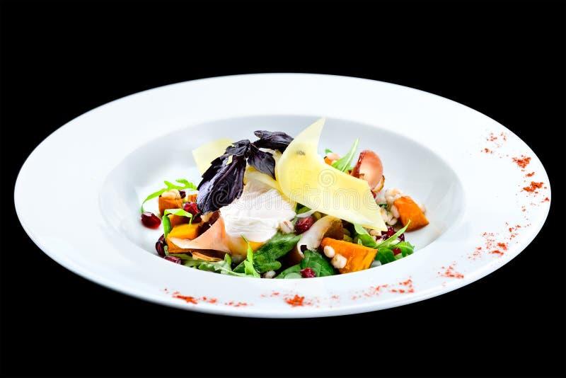 Insalata saporita e deliziosa con la zucca al forno in un isola bianco del piatto fotografie stock