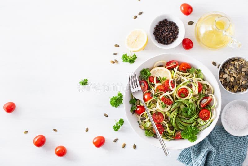 Insalata spiralized ketogenic dello zucchino del vegano con i semi di zucca del pomodoro dell'avocado fotografie stock