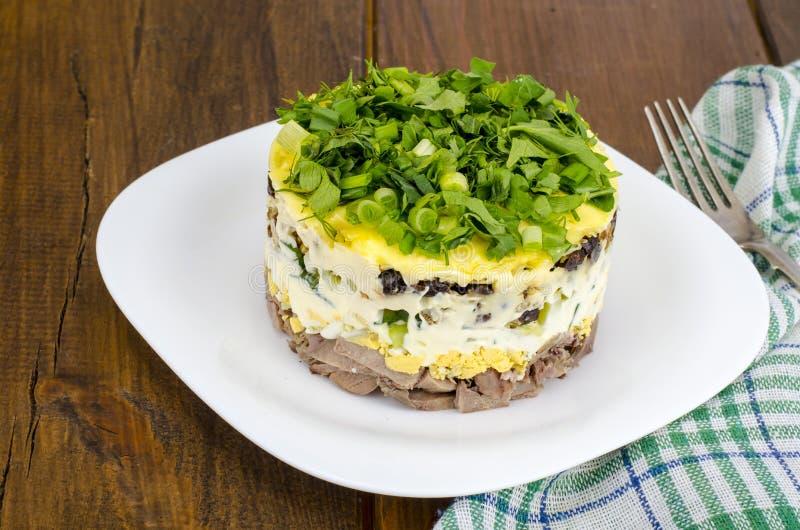 Insalata stratificata della parte con carne, il cetriolo, l'uovo e la maionese immagine stock