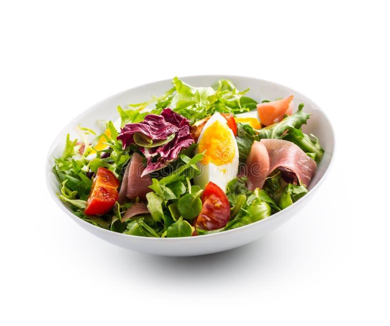 Insalata su bianco una ciotola di insalata fresca della lattuga con i pomodori eggs il prosciutto di Parma sopra bianco immagini stock libere da diritti