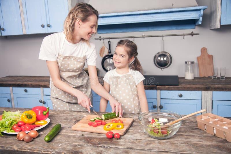 Insalata sveglia del taglio della figlia e della madre nella cucina fotografie stock
