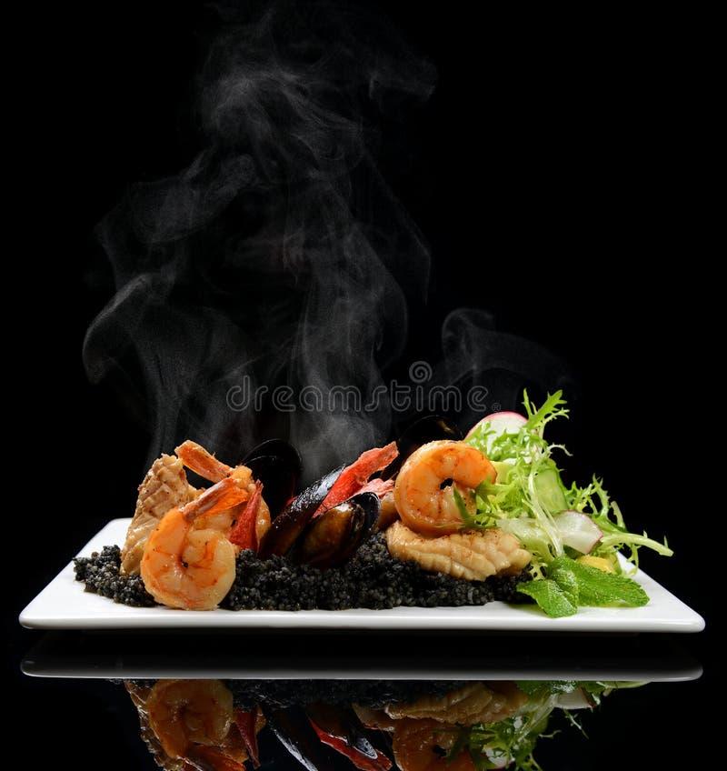 Insalata tailandese dei frutti di mare piccanti caldi su un letto del preparato nero dell'insalata e del caviale con le cozze ed  fotografie stock