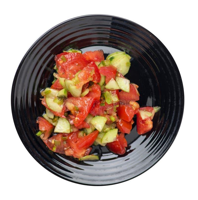Insalata vegetariana con i cetrioli, i pomodori e le cipolle verdi insalata del vegano su un piatto isolato su fondo bianco Prima immagine stock