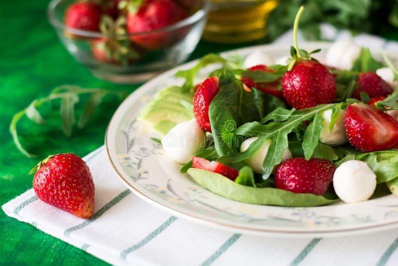 Insalata vegetariana fresca con spinaci, rucola, le fette di avocado, le fragole e la mini mozzarella immagini stock