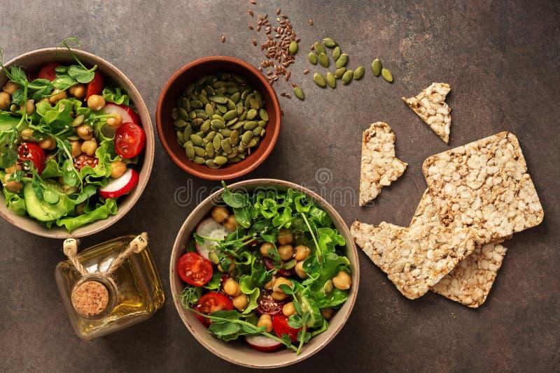 Insalata vegetariana sana del vegano con i ceci, gli ortaggi freschi, i semi di zucca e gli interi pani croccanti del grano su un fotografia stock