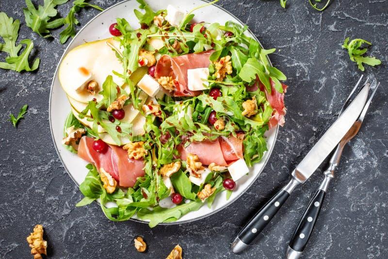 Insalata verde con formaggi arugula, pera, jamon e feta su fondo di pietra scura Vista dall'alto immagine stock libera da diritti