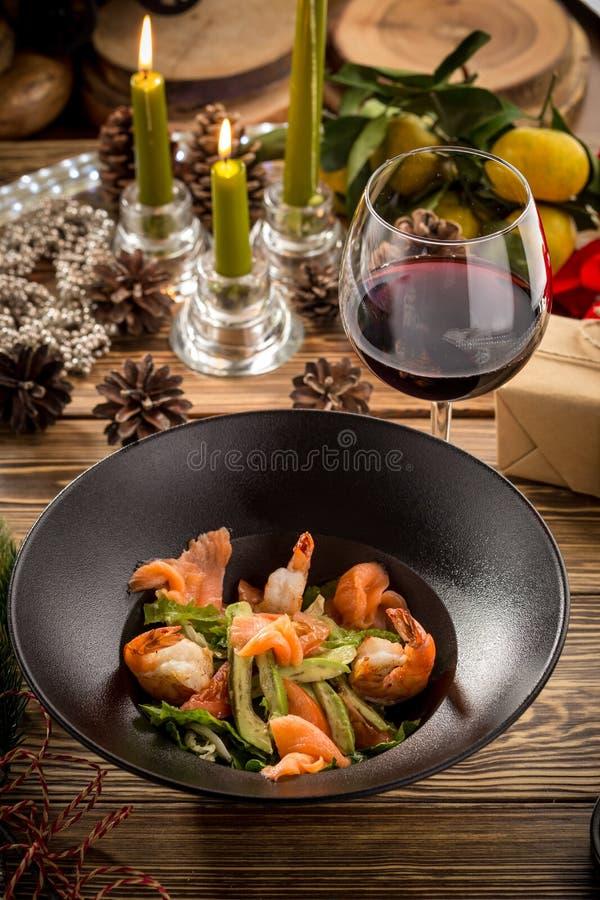 Insalata verde dei frutti di mare con il salmone, avocado e gamberetti e vetro di vino rosso su fondo decorato natale immagini stock