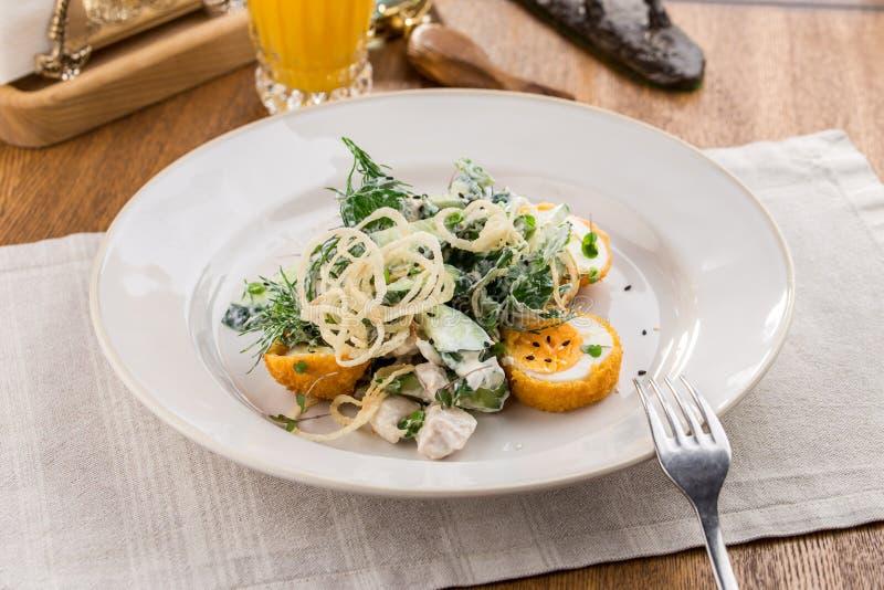 Insalata verde mista fresca con l'uovo ed il vetro di succo d'arancia sulla tavola di legno fotografia stock