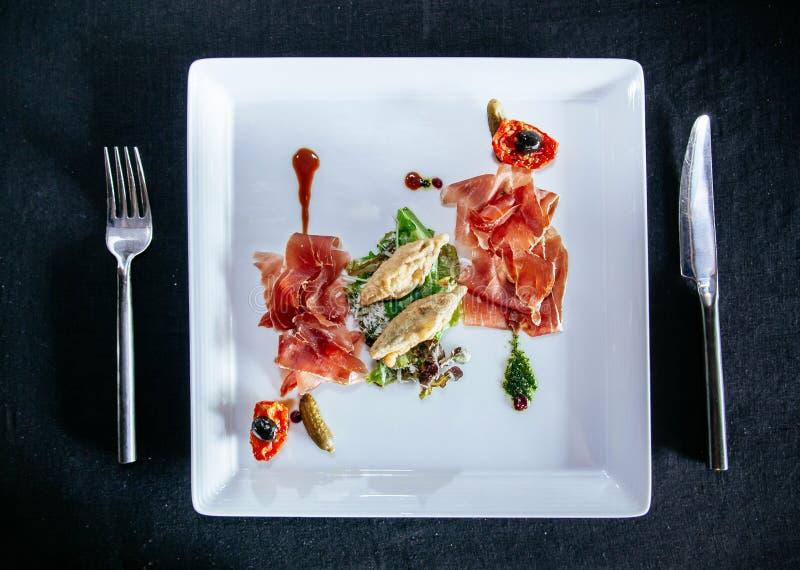 Insalata verde saporita della miscela con il prosciutto di prosciutto di Parma, pomodoro seccato al sole, blac fotografie stock libere da diritti