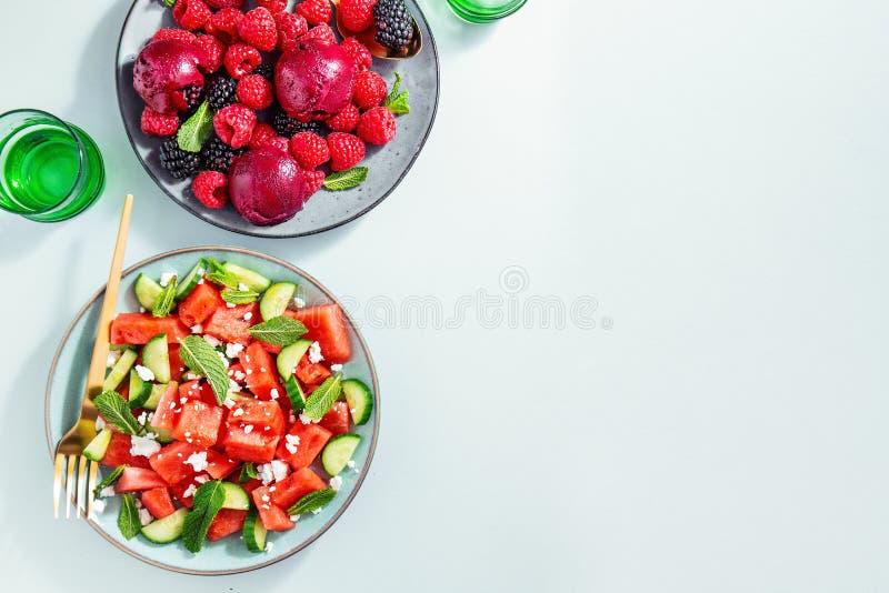 Insalate di estate con l'anguria e cetrioli, bacche e gelato fotografie stock
