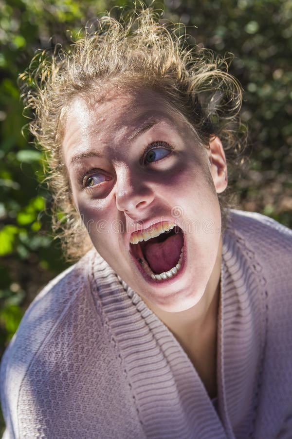 Insane woman screaming. Young mad caucasian girl deranged and screaming royalty free stock photos