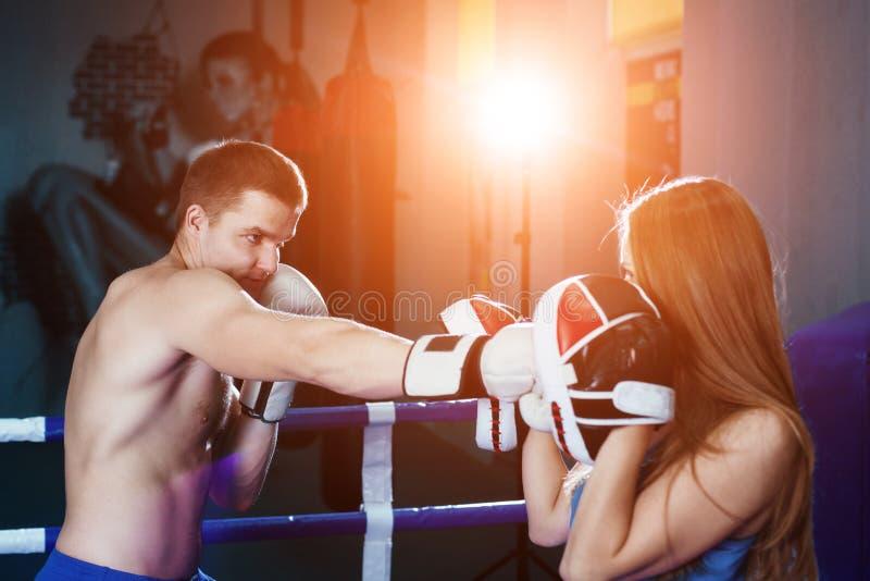 Inscatolamento di pratica delle coppie sportive femminili e del maschio alla palestra al ring immagini stock libere da diritti