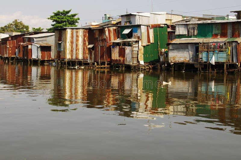Inscatoli le baracche lungo un fiume, quasi sprofondante fotografia stock