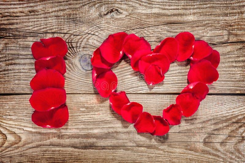 Inschrijving I liefde met roze bloemblaadjes wordt geschreven dat stock fotografie