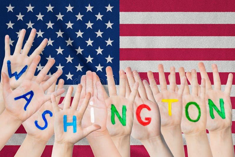 Inschrijving Washington op de handen van de kinderen tegen de achtergrond van een golvende vlag van de V.S. stock foto