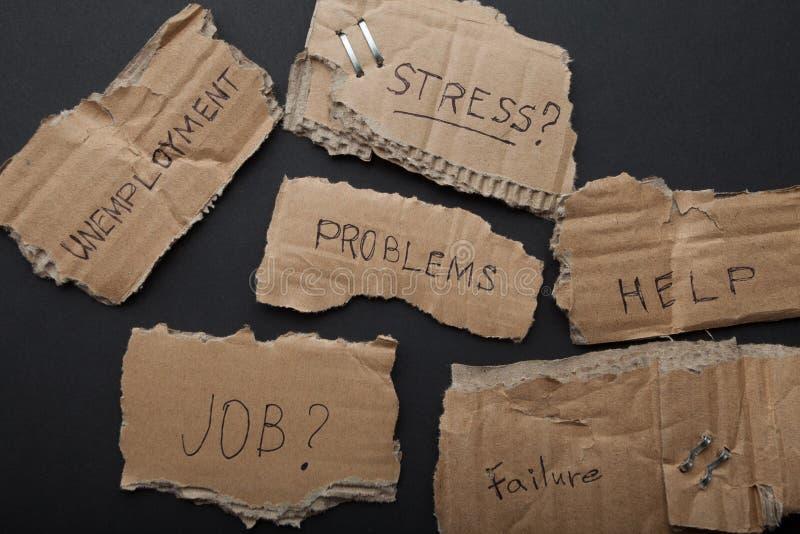 Inschrijvingen op kartonplaten op een zwarte achtergrond: problemen, hulp, het werk, fout, werkloosheid, spanning stock foto