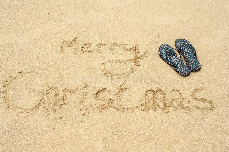 Inschrijvings Vrolijke Kerstmis op het strand in de zand en strandpantoffels stock fotografie