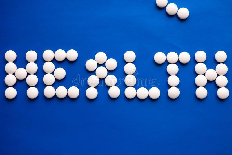 Inschrijvingsgezondheid van witte pillen op blauwe lijst wordt gemaakt die Het concept van de geneeskunde stock afbeeldingen
