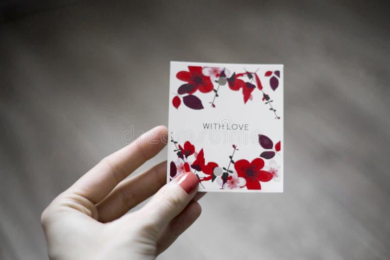 A inscrição 'com amor 'em um fundo branco com flores, uma mão com o papel assinado Fundo de madeira imagem de stock