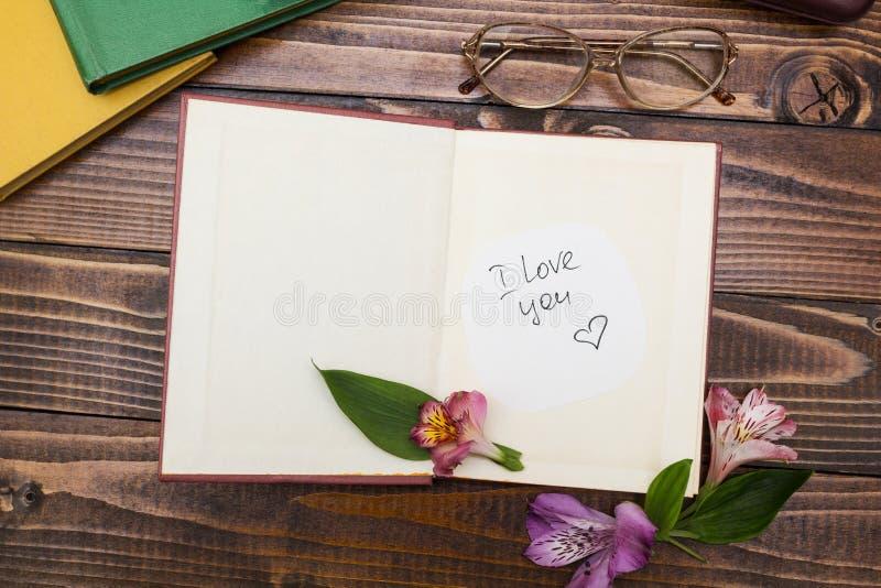 A inscrição 'eu te amo 'em um livro aberto com flores, vidros aproxima-se fotografia de stock royalty free