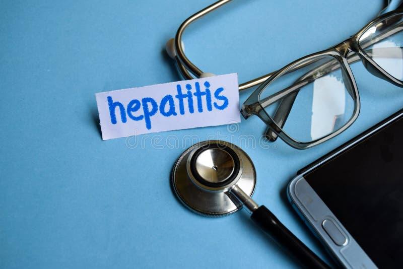 Inscrição da hepatite com a vista do estetoscópio, dos monóculos e do smartphone no fundo azul imagens de stock royalty free